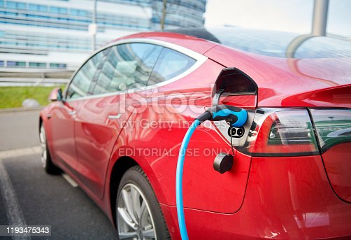 Duesseldorf, Germany- December 10. 2019: A red Tesla Model S is parked in a business destrict of Duesseldorf and is connected with a blue power chord to a recharging station, a modern office buidling in the background.