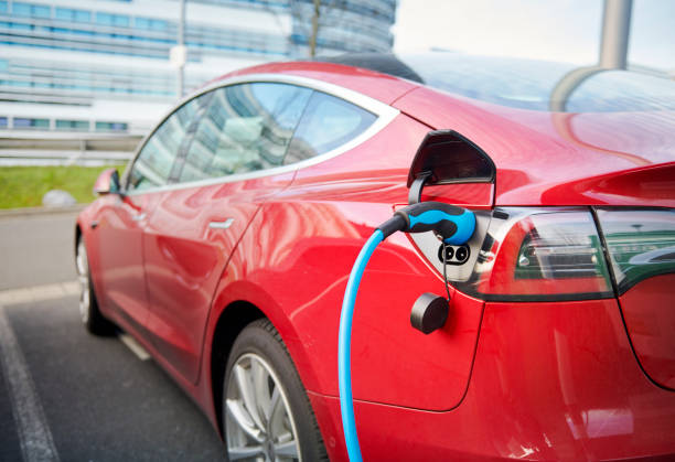 Red Tesla Model S electric car connected to a recharging station Duesseldorf, Germany- December 10. 2019: A red Tesla Model S is parked in a business destrict of Duesseldorf and is connected with a blue power chord to a recharging station, a modern office buidling in the background. tesla model s stock pictures, royalty-free photos & images