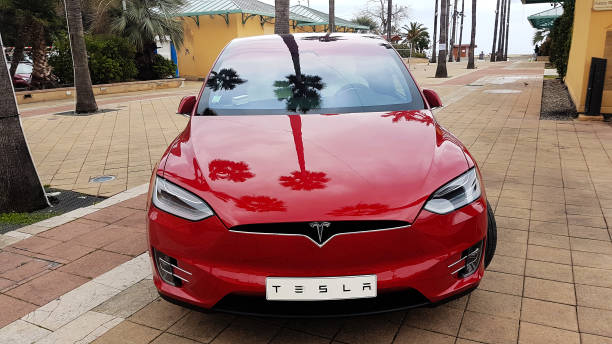Red Tesla Model X Electric SUV Front View Menton: Red Tesla Model X Electric Car Parked on a Square in Menton on The French Riviera. Tesla Model X is a Luxury Full-Sized SUV, All-Electric Crossover tesla motors stock pictures, royalty-free photos & images