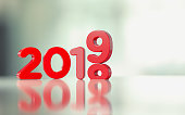 Red text changing from 2018 to 2019 on reflective surface over defocused background. Change and new year concept. Horizontal composition with copy space.