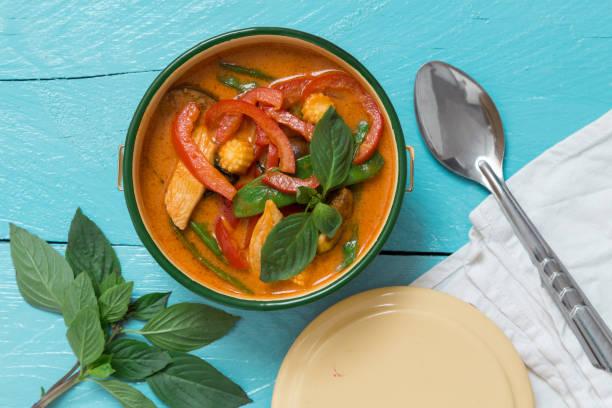 red thai curry in einer schüssel auf türkis holztisch - ocimum tenuiflorum stock-fotos und bilder