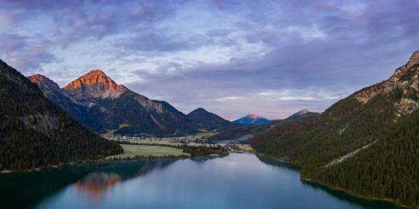 roter thaneller Berggipfel bei Morgendämmerung und Reflexion im Heiterwanger See im Herbst – Foto