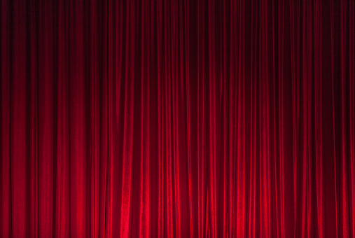 Background of red spotted real theatrical velvet curtain or drapes texture