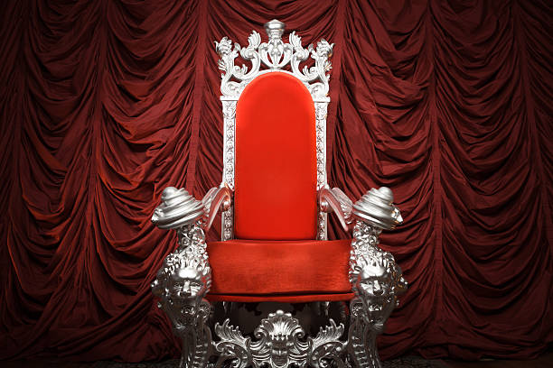 Red Throne A costume prop chair in front of red drape. royalty stock pictures, royalty-free photos & images