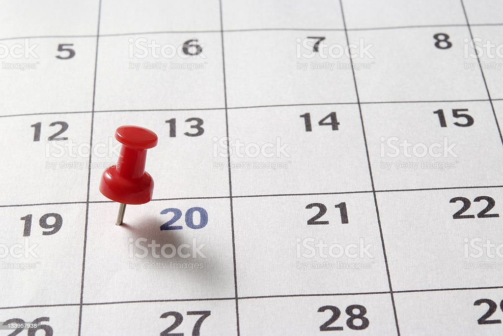 Red thumbtack in calendar with shadow royalty-free stock photo