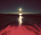 A red tide washes onto a beach in Moonlight.  Long exposure.