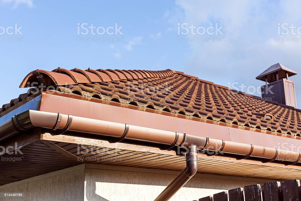 Red tiled roof with gutter and chimney stock photo