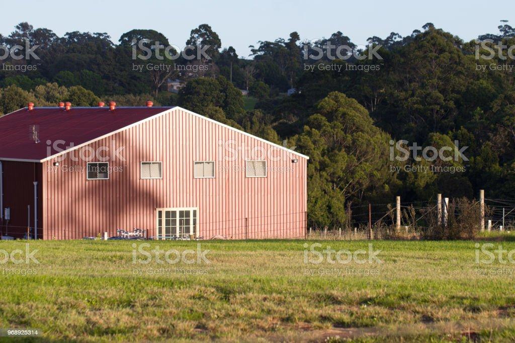 Casa de madeira vermelho celeiro no paddock de gramínea fazenda verde - foto de acervo