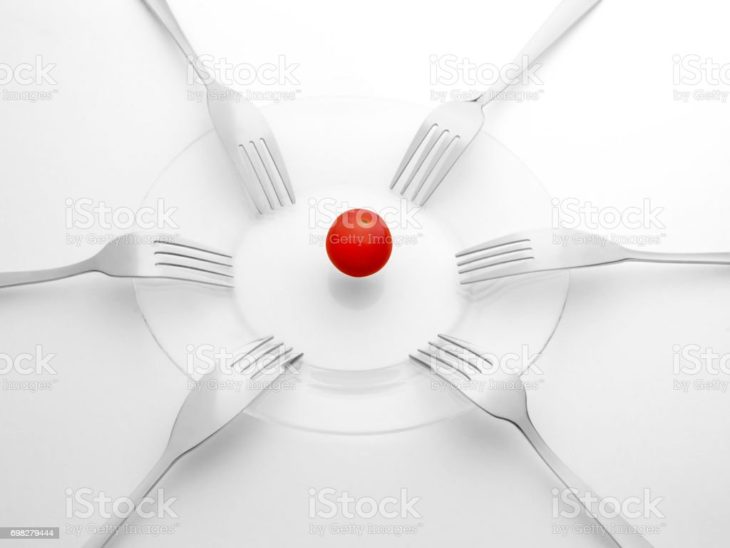 Red tomato and six black and white forks. Sharing, competition, shortage and contention concept. stock photo