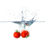 Red Tomato Fruits Sinking in Water Isolated on White Background