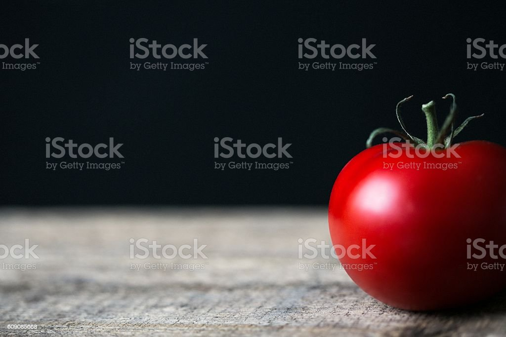 Red tomato on the rustic table in dark kitchen stock photo
