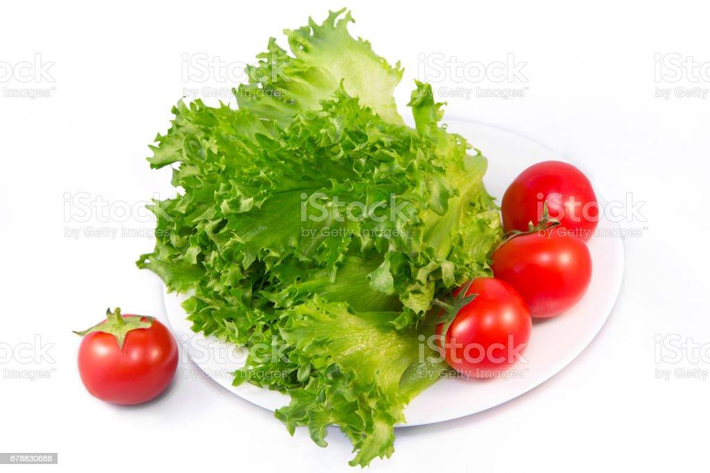 Kırmızı domates ve yeşil salata (ortak marul) bir beyaz üzerine plaka ve beyaz arka plan üzerinde izole royalty-free stock photo