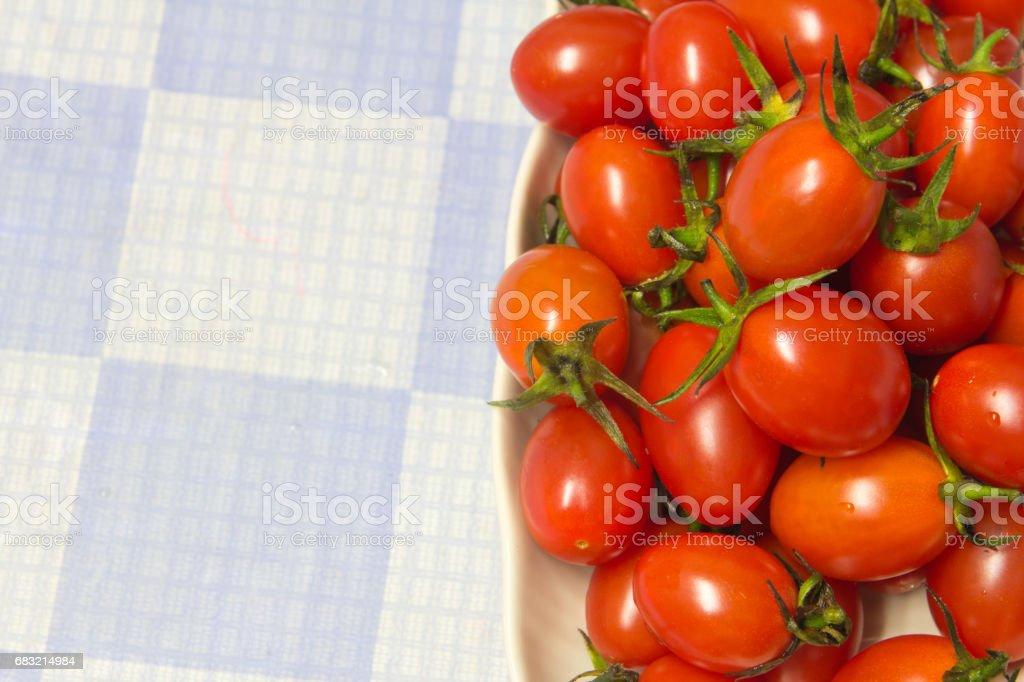 紅番茄放在白色的陶瓷盤子,放在白色和藍色的格子板桌。 免版稅 stock photo