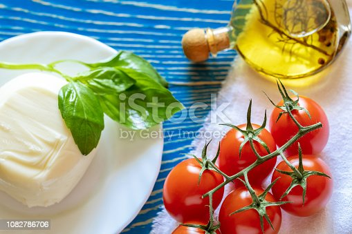 istock Red tomatoes, mozzarella cheese, olive oil and Basil on white kitchen napkin on blue wooden table. 1082786706