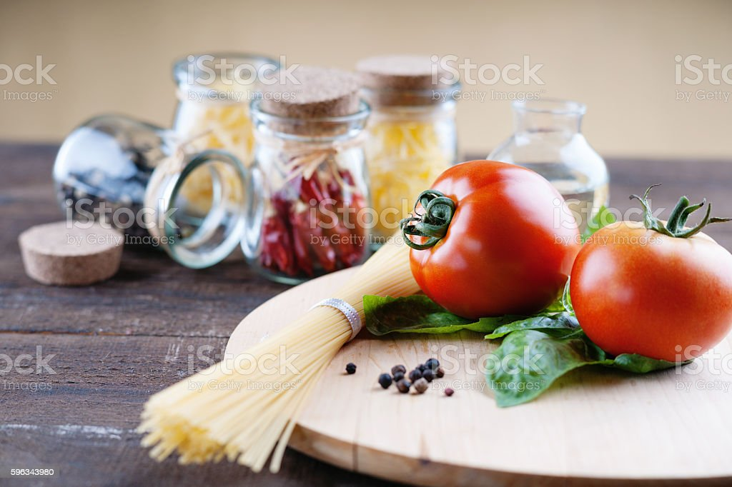 Red tomatoes on a cutting board and pasta Lizenzfreies stock-foto