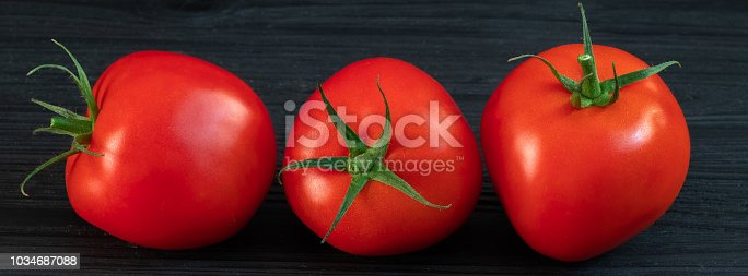 red tomatoes on a green branch on a black wooden background.