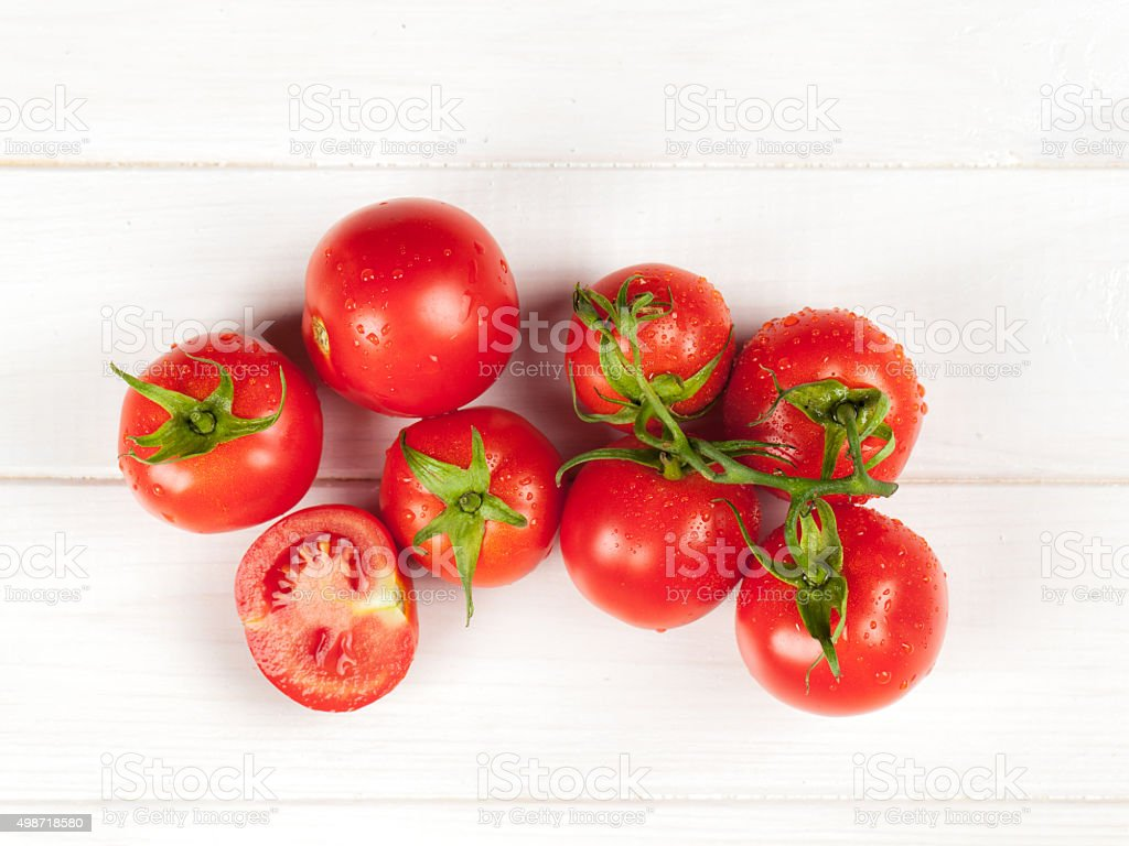 red tomatoes on wooden table stock photo