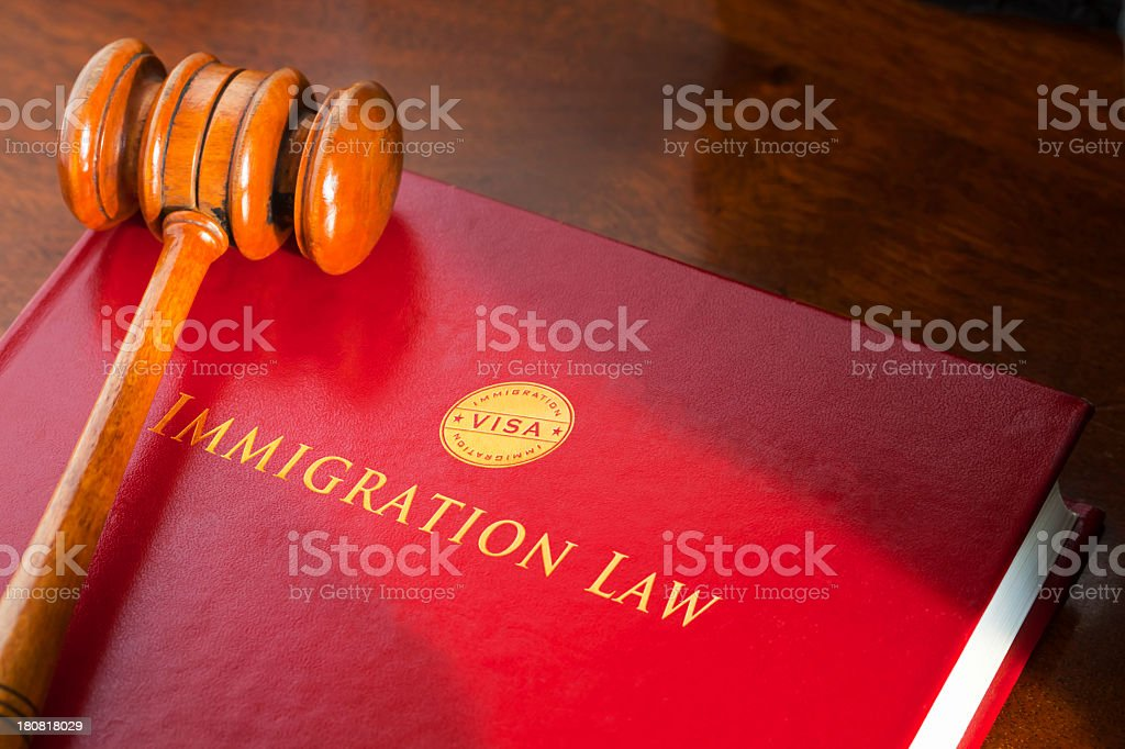 A red tome covering immigration law and a judge gavel on it stock photo