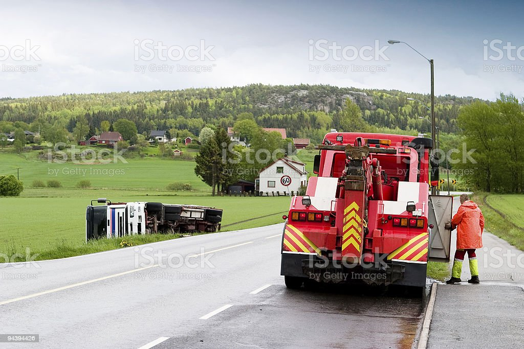 A red tow truck cleaning a rural town's highway stock photo