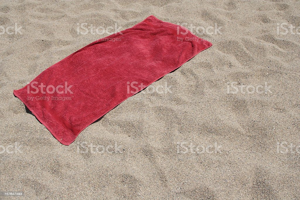 Red towel left on sandy beach stock photo