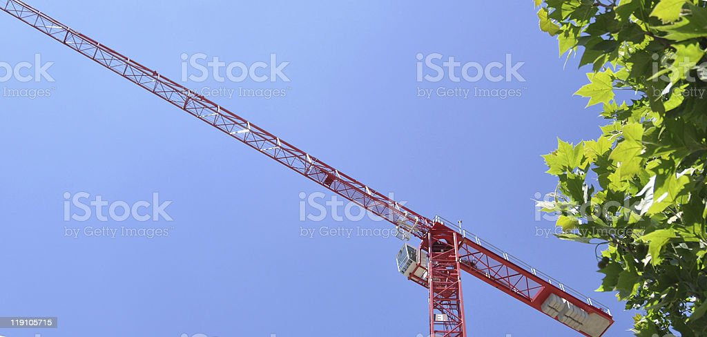 Red tower construction crane with bushes royalty-free stock photo