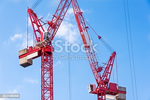 Two red tower cranes against the sky, London, UK.