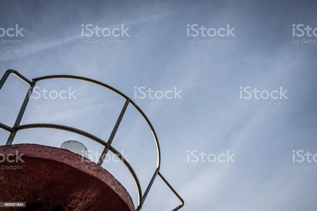 Red tower with chrome circular railing against the sky foto de stock royalty-free