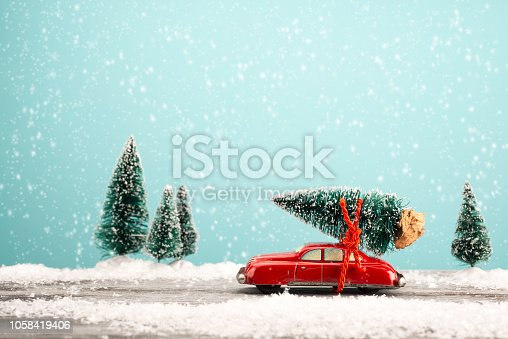 Red toy car carrying a Christmas tree in a snowy landscape. Space for text.