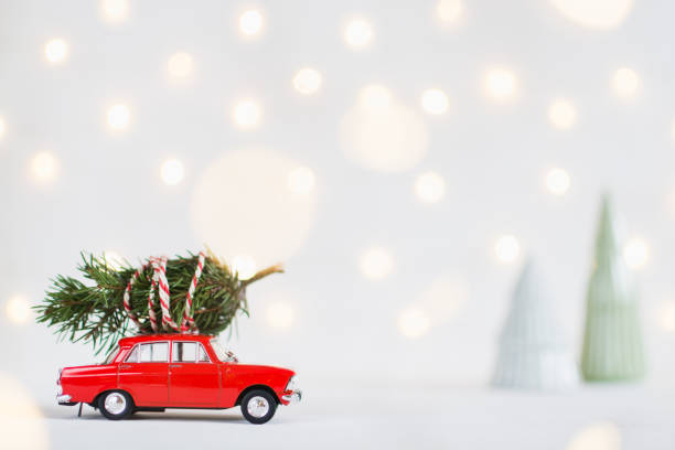 red toy car with a christmas tree on the roof, garland bokeh on background - christmas background стоковые фото и изображения
