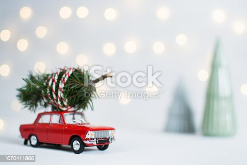 Red toy car with a christmas tree on the roof, garland bokeh on the background, shallow depth of field.