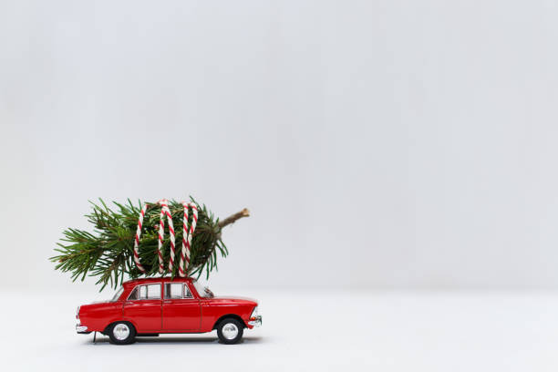 red toy car with a christmas tree on the roof - christmas background стоковые фото и изображения