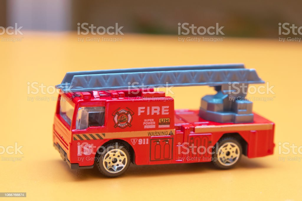Red toy fire truck Toy fire engine extinguishes flaming house....