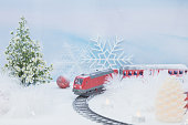 A red toy train on plastic rails on snow field with cutter flowers tree and red ball with blue sky background.