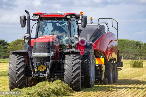 Kirwee, Canterbury, New Zealand, March 27 2019: A Case baler and tractor at work making hay bales at the South Island Agricultural Field Days event