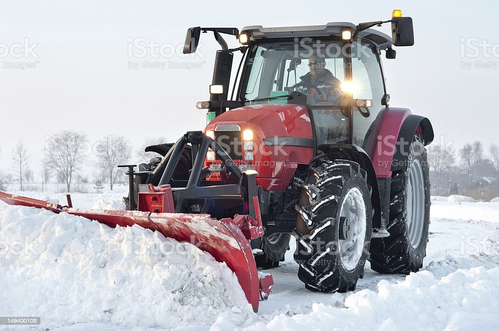 A red tractor cleaning snow from a road royalty-free stock photo
