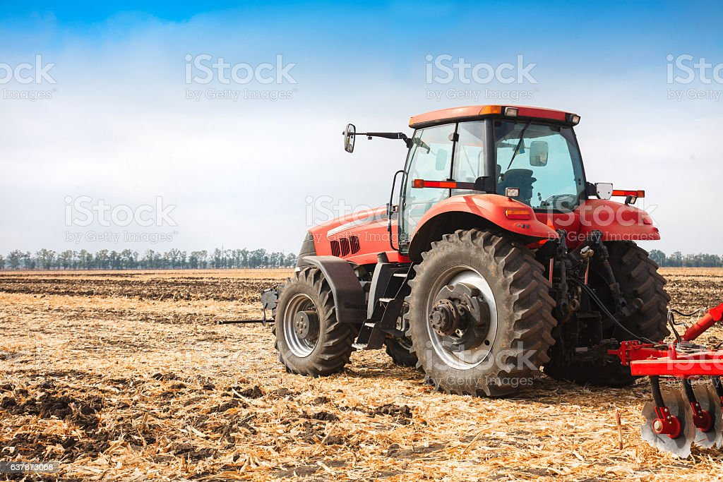 Red tractor in the field on a bright sunny day. stock photo