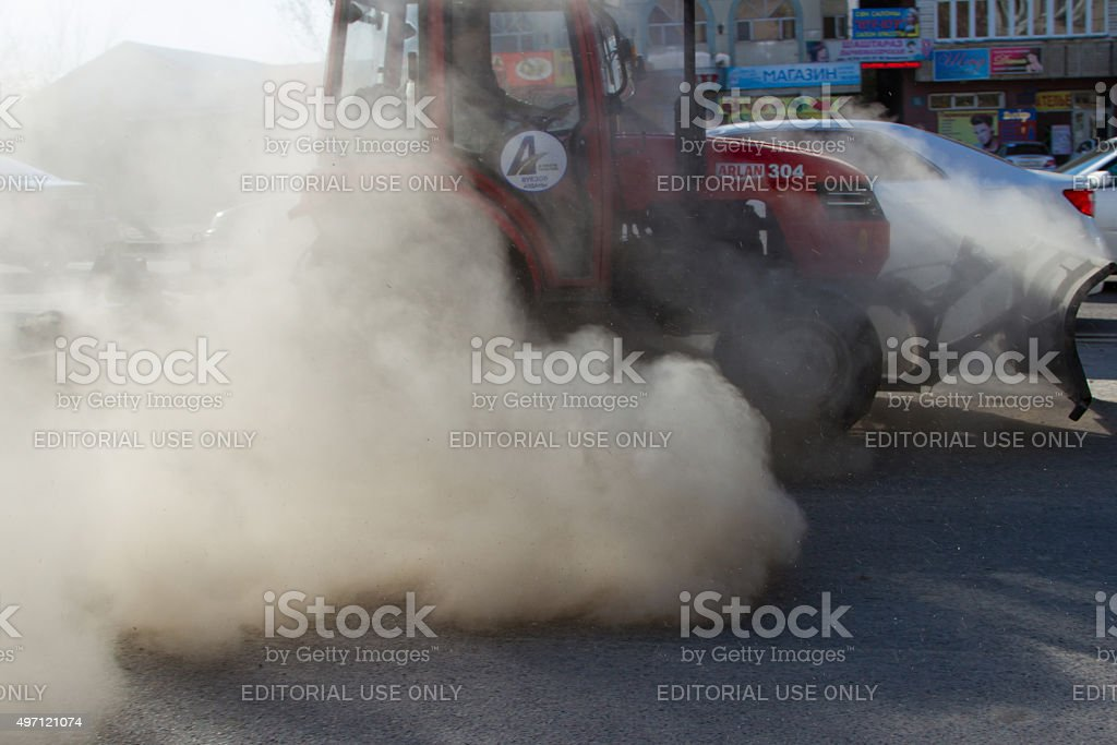 red tractor is sweeping the road stock photo