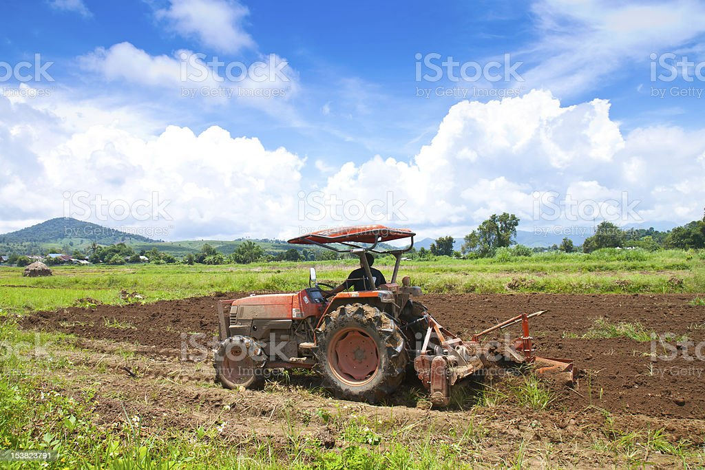 Red tractor parked on a grass field royalty-free stock photo
