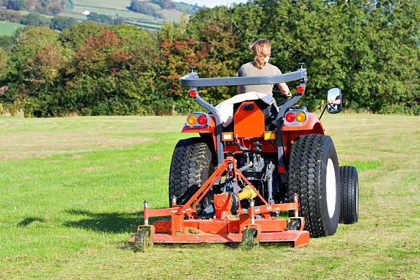 red tractor - riding lawn mower stock photos and pictures