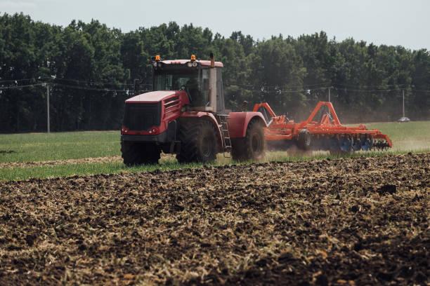 roter Traktor mit großen Rädern im Feld während der Tests während der Ausstellung in Russland – Foto