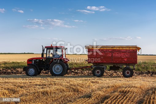 Red tractor with red trailer ina field