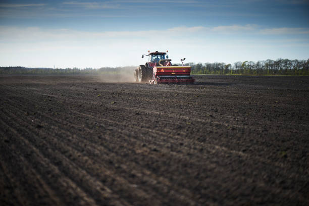 Red tractor with sowing machine on a ploughed field stock photo