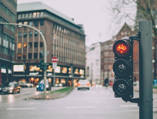 rote ampel für fahrräder (fahrräder). verschwommene stadtbild auf hintergrund. - reifen hamburg stock-fotos und bilder