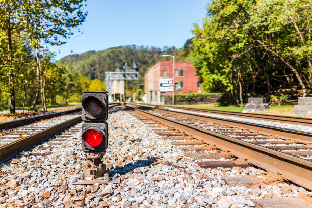 red traffic light for train with metal iron railroad tracks in thurmond, west virginia with nobody in abandoned ghost town - railway signal stock photos and pictures