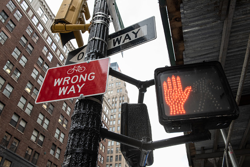 Corner of a city street with caution signs that have a Red Hand to stop, a red sign and a One Way sign.