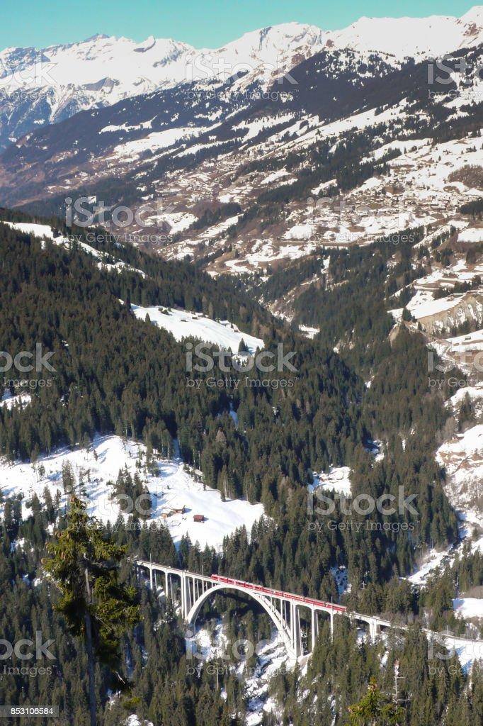 red train crossing a bridge in the Swiss Alps near Arosa stock photo
