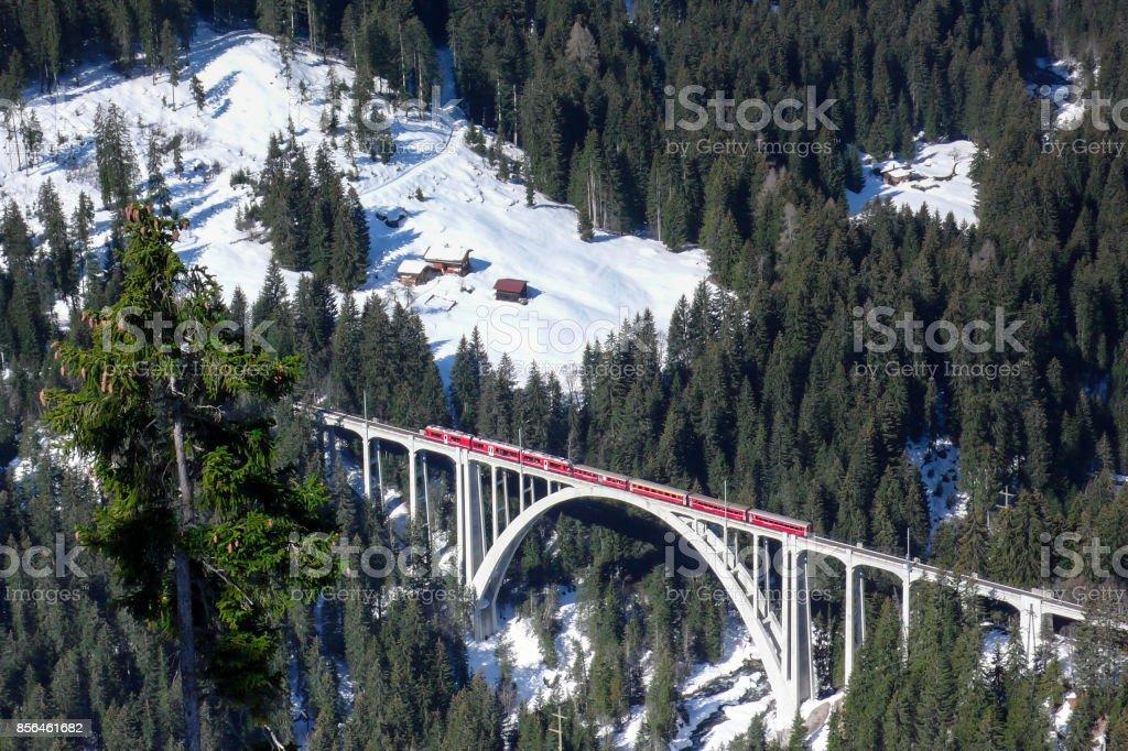 red train crossing a bridge stock photo