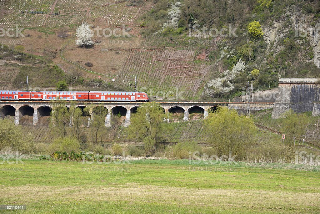Red train drives on Viaduct  through vineyards heading for tunnel royalty-free stock photo