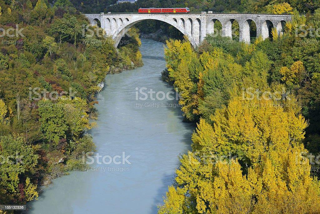 Red Train on Bridge over Soca River Slovenia A red train passing over a stone-arched bridge over the Soca River; Slovenia, Europe. Arch Bridge Stock Photo