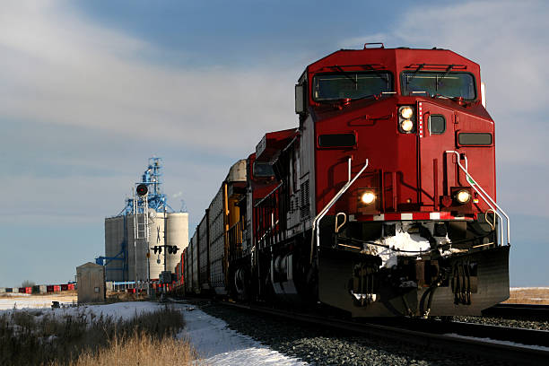 red train on tracks in alberta, canada - godståg bildbanksfoton och bilder